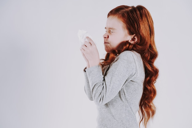 Red haired teen sneezes, on grey background.