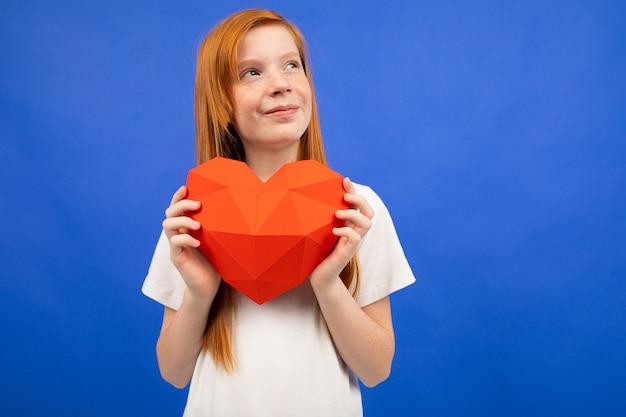 コピースペースと青い紙で作られた赤いハートを保持している赤い髪の10代の少女