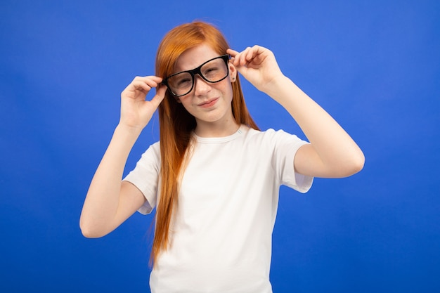 Red-haired teenage girl in a white t-shirt squinting holding glasses in his hand blue