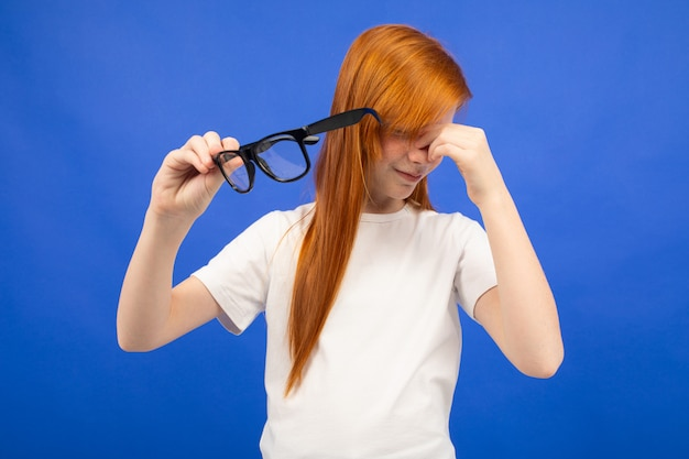 Red-haired teenager girl squints while holding glasses in her hand blue