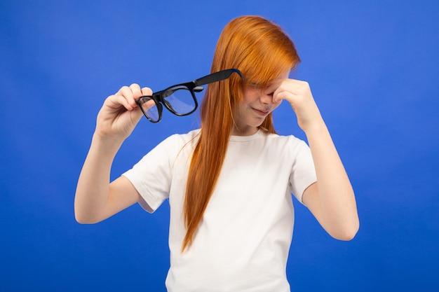 赤い髪のティーンエイジャーの女の子は彼女の手で眼鏡を押しながら青い目を細める