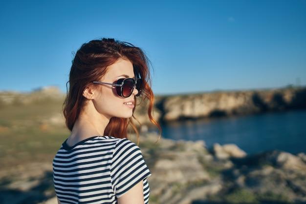 眼鏡をかけた赤毛の旅行者は、海の風景の近くの山で休んでいます