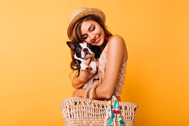 Red-haired white girl posing in studio with her pet. good-looking young lady in hat holding french bulldog on bright.