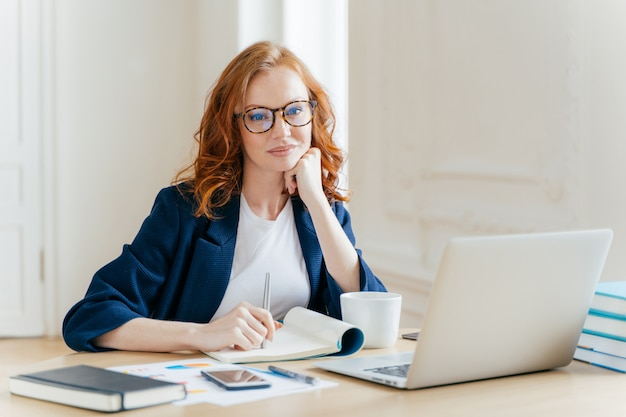 Red-haired woman analyzes data and makes accounting report