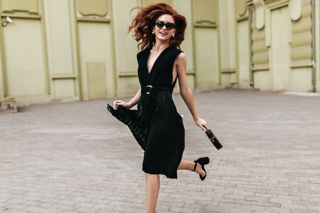 Red haired woman in dark green dress running outside