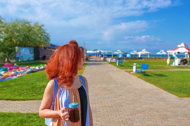 Red-haired woman in a dress and a backpack drinking smoothies on the beach