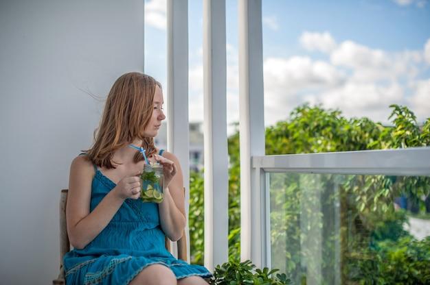 Рыжая женщина пьет мохито на террасе