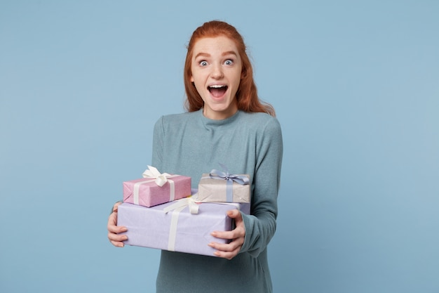 Red-haired woman holding boxes with gifts in her hands, stands sideways with wide open eyes