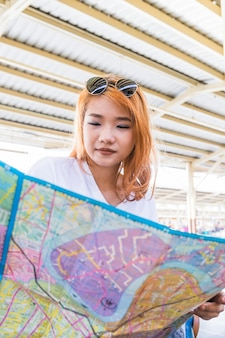 Red haired woman holding map
