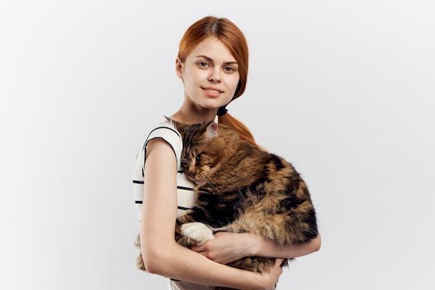 Рыжая женщина держит в руке кота в полосатой футболке на светлом фоне домашнего питомца