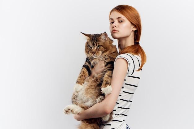 Рыжая женщина держит в руке полосатую кошку, футболку с легким домашним питомцем. фото высокого качества