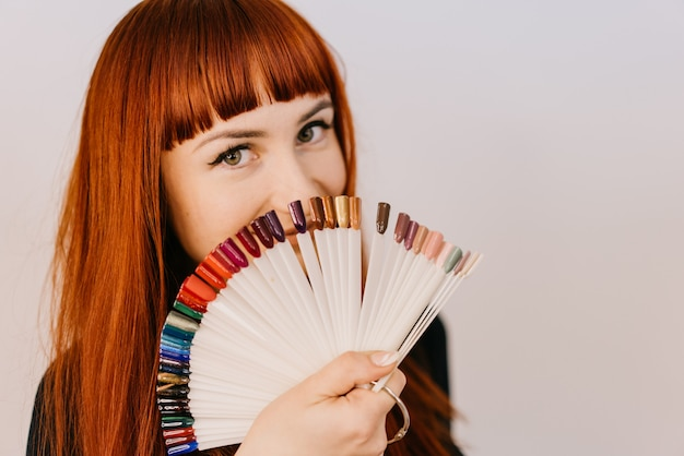 Red-haired woman holds samples of a gel-varnish in her hand in the form of a semicircle on white.