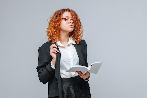 Рыжая женщина в черной куртке и очках читает белую книгу