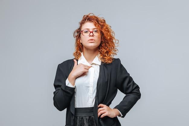 Рыжая женщина в черной куртке и очках