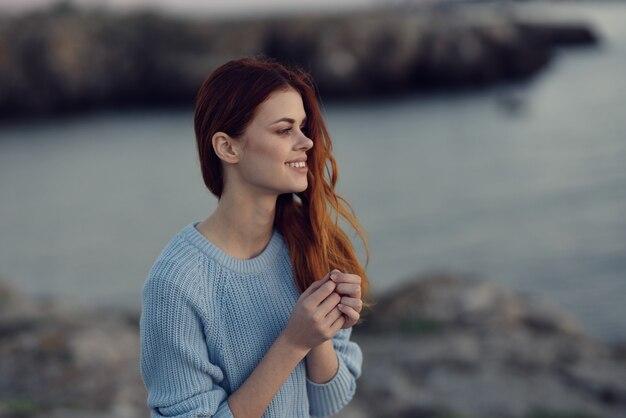 自然の中で川の近くの青いセーターを着た赤毛の女性。高品質の写真