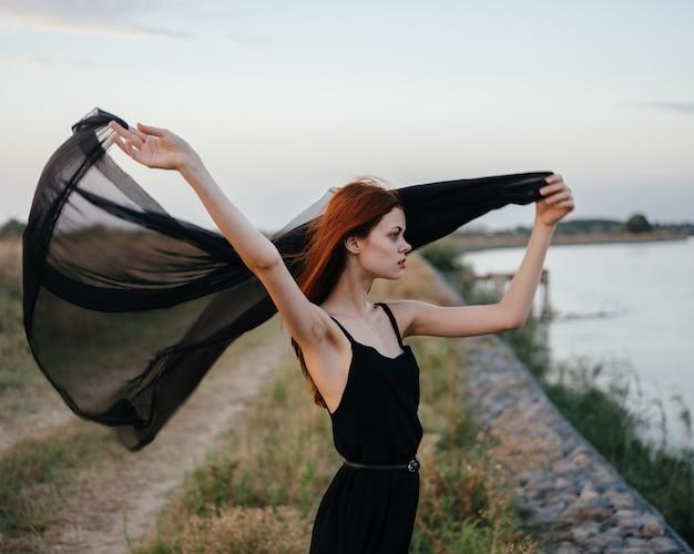 Рыжая женщина в платье с черной тканью на дороге у реки. фото высокого качества