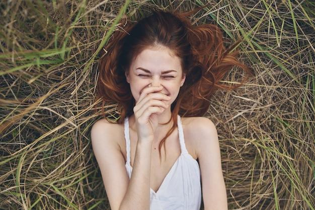 白いドレスを着た赤毛の女性は、干し草の山の屋外の新鮮な空気のモデルに横たわっています。