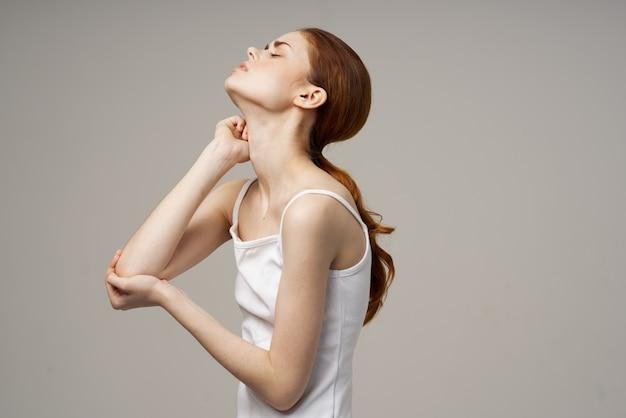 Рыжая женщина в белой футболке на бежевом фоне жестикулирует болью в локте. фото высокого качества