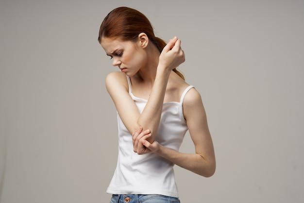 Рыжеволосая женщина в белой футболке на бежевом фоне показывает руками боль в локте