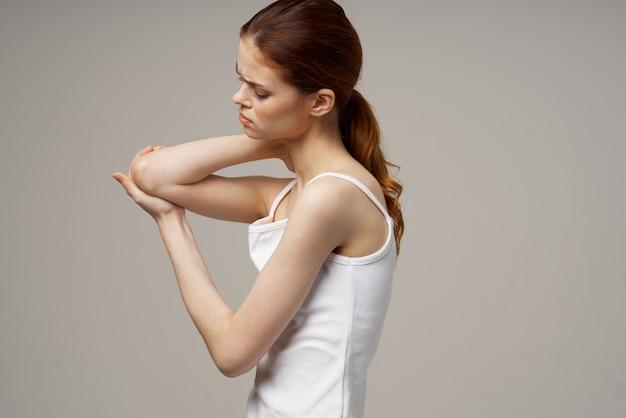 Рыжеволосая женщина в белой футболке на бежевом пространстве жестикулирует руками боль в локте