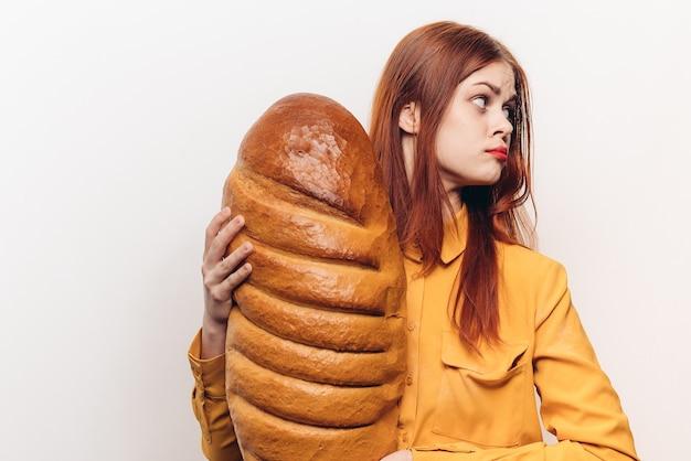 黄色いシャツを着た赤毛の女性パンを手に小麦粉製品の明るい背景コピースペース。高品質の写真