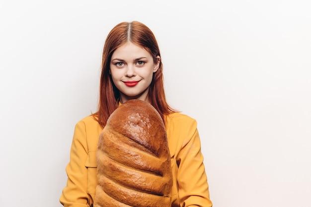 黄色いシャツを着た赤毛の女性パンを手に小麦粉製品ライト