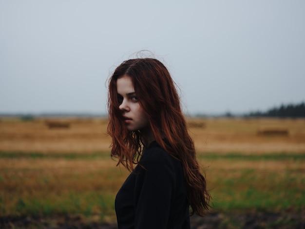 フィールド風景ポーズで黒のドレスを着た赤髪の女性。高品質の写真