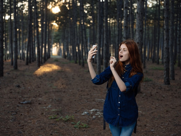 森の自然の中の赤毛の女性は、自由に歩きます。高品質の写真