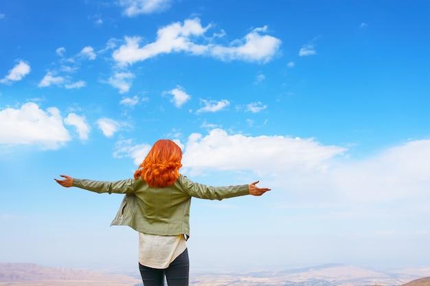 緑のジャケットの赤髪の女性は屋外の手を開く