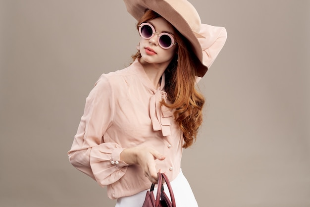 帽子とベージュのメイクのシャツに赤髪の女性は魅力的な若者のファッションを笑顔します。