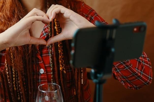 잠옷과 의료용 마스크를 쓴 빨간 머리 여성은 스마트폰 웹캠을 사용하여 온라인 화상 통화를 하고 있으며, 멀리서 격리 사랑에 하트 발렌타인 데이 모양으로 접힌 손으로