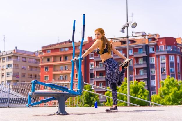 보라색 레깅스와 검은색 작업복을 입은 빨간 머리 여성이 운동을 하고, 기계에서 스트레칭을 하고, 도시에서 스포츠를 합니다.