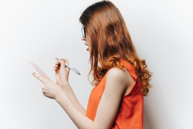 メモ帳チャームメガネファッションライトとシャツの赤髪の女性。