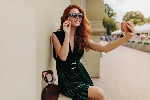 Selfie를 복용하는 세련 된 선글라스에 빨간 머리 여자