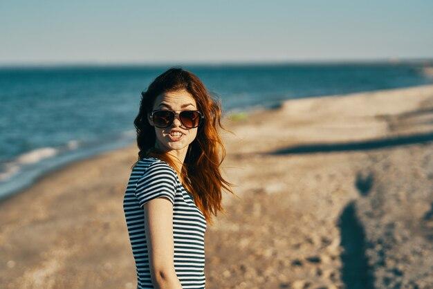 海の新鮮な空気の休暇の側面図の近くのビーチでサングラスをかけた赤毛の女性