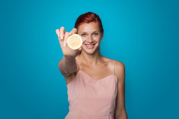 빨간 머리 여자는 슬라이스 레몬 카메라에 보이고있다