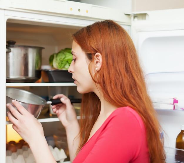 냉장고에서 뭔가를 찾고 나가서는 여자