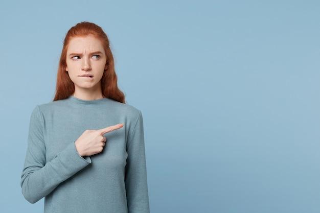 赤毛の女性が人差し指で唇のショーを慎重に噛んでいる疑いで横を向いている