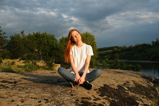 Red-haired woman meditates and relaxes in nature outdoor rocks at sunset.