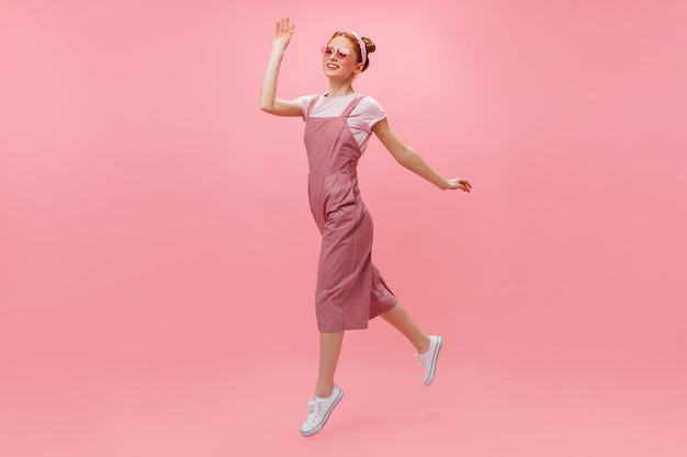 Red-haired woman in overalls and glasses joyfully moves on pink background.