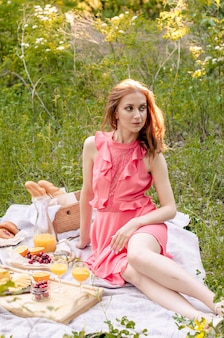 The red haired woman in pink dress with glass of orange juice.