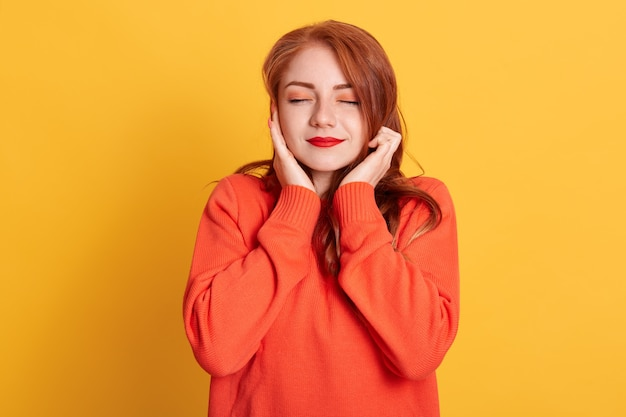 Red haired woman plugging ears with fingers and closing her eyes, not wanting to listen hard loud music