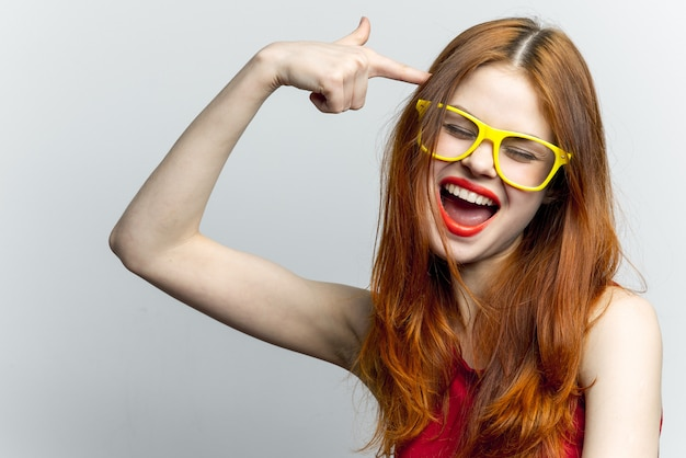 Red-haired woman in a red dress and yellow glasses, white