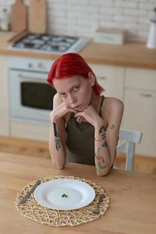 Рыжая женщина. рыжая женщина с анорексией сидит на кухне, плохо себя чувствует и голодна