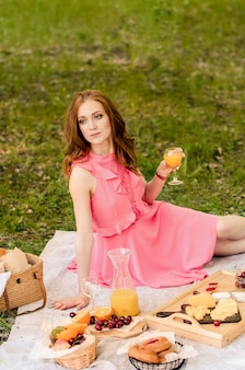 The red haired woman rest in pink dress with glass of orange juice.