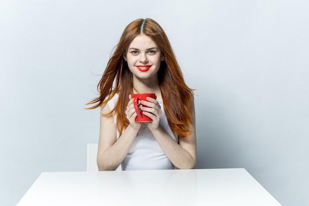 Рыжая женщина сидит за столом с расслабляющей чашкой напитка