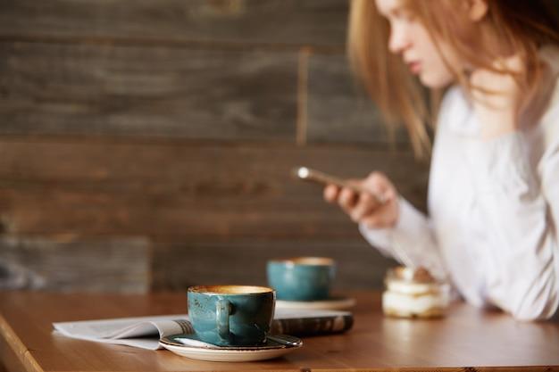 カフェに座っている赤毛の女性