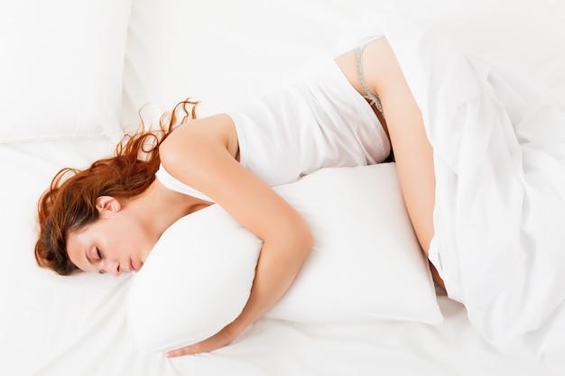 Donna dai capelli rossi dormire sul foglio bianco