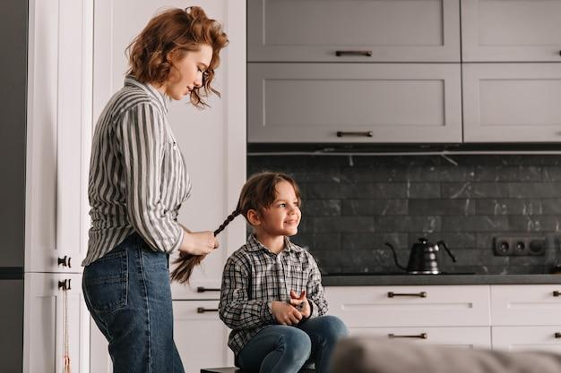 La donna dai capelli rossi in camicia a righe intreccia le trecce alla bambina sorridente.