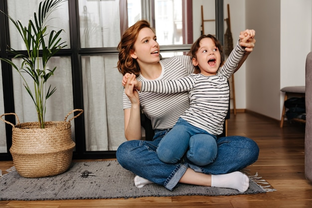 Red-haired woman in striped t-shirt hugs her daughter and plays with her sitting on floor in living room.